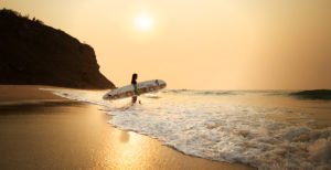 Woman on the beach with surfboard